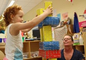 Hilltop Elementary School Universal Pre-K student Tatum Dougherty builds a block skyscraper in the classroom while Belinda Merinar, grandmother, supervises the construction.