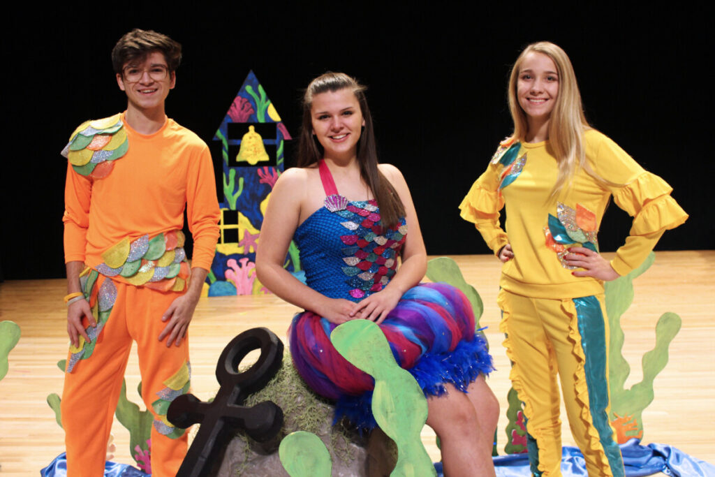 Rainbow Fish (played by Emily Anderson) is flanked by two fish played by Logan Montz and Sydney Hess in Monarch Company's production of The Rainbow Fish Musical.