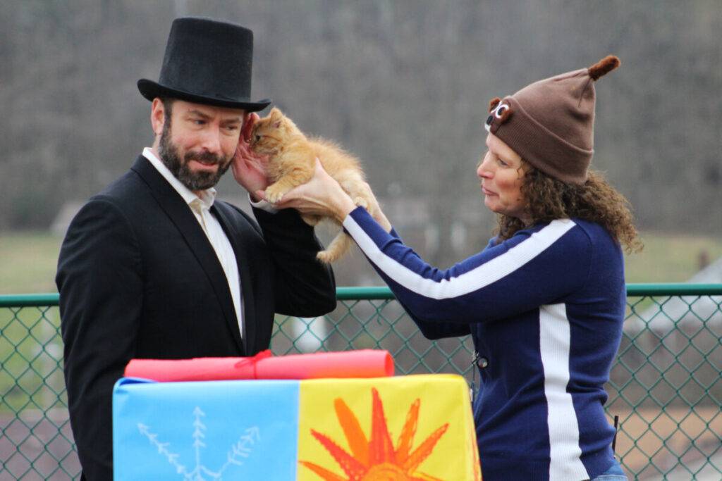 From left: WLES PE teacher Michael Grimm gets Wildcat Wally's prediction whispered to him while WLES Speech Therapist Becky Hinerman holds the kitten to his ear.