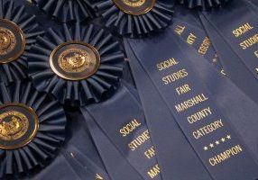 Blue ribbons with gold lettering that says Marshall County Social Studies Fair