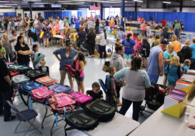 Wide shot of the vendors along with students getting their school supplies.