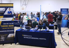 Students and adults talk to college and business representatives at the JMHS College and Career fair.
