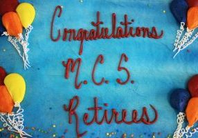 "Blue cake with ""Congratulations MCS Retires"" written in red icing. There are yellow, orange, blue and red icing balloons on the sides of the cake."