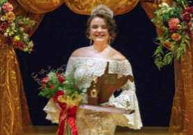Madilyn Blake holding her trophy while wearing her crown on stage following the JM Queen of Queens pageant.