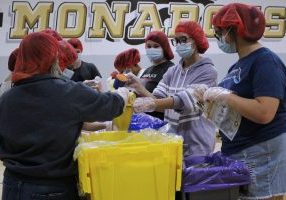 Students, faculty, staff and administrators packed shelf-stable meals, assembly-line style while wearing red hairnets.