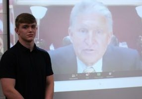 Ian Bush, wearing a black shirt, stands in front of a projector screen with Senator Manchin talking during the teleconference.