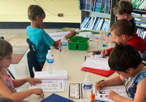 Students are coloring while sitting at a table.