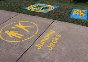 yellow paint on the sidewalk that says jumping jacks