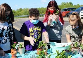 Several members of the Hilltop Elementary School Kindness Crew show off the flowerpots they painted and filled with plants that will be given to residents at Stonerise Moundsville.