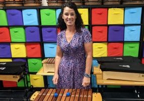 Kathy Fox is pictured wearing a purple dress standing in front drums and playing the xylophone.
