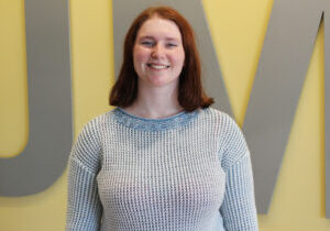 Leah standing in front of a yellow wall. She is wearing a gray sweater.