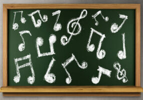 green chalkboard with white music notes written in chalk