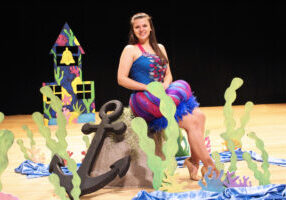 The Rainbow Fish, played by Emily Anderson, is sitting on a rock in her multicolored costume for the musical.