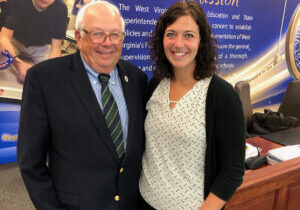 From left: WV BOE member Dr. James Wilson and McNinch Primary School 1st grade teacher Heather Haught pose for a picture in the lobby of the West Virginia Department of Education.