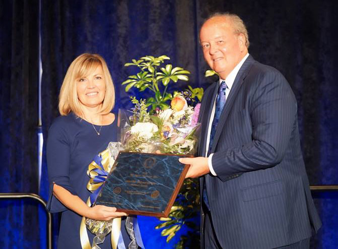 """West Virginia Superintendent of Schools Steven Paine presents CHS Science teacher Jennifer Schwertfeger with the """"WV Teacher of The Year"""" plaque during a ceremony Wednesday night in Charleston."""