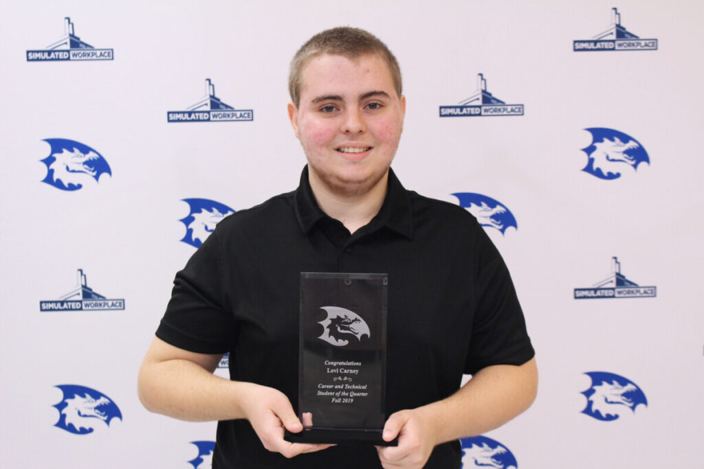 Levi Carney poses with his CTE Student of the Quarter plaque.