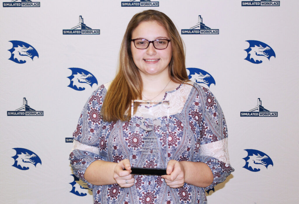 Ashlee Evans holds her CTE Student of the Month plaque.