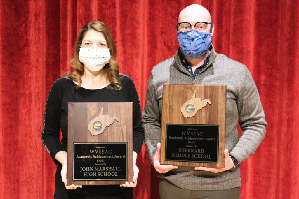 Pictured from left: JM Band Director Tracey Filben and SMS Band Director Jason Burch display their schools' award. They are standing in front of a red stage curtain.