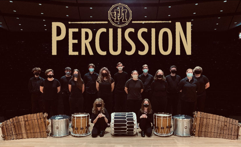 Group picture on the CPA stage with JM Percussion in gold lettering at the top of the picture.