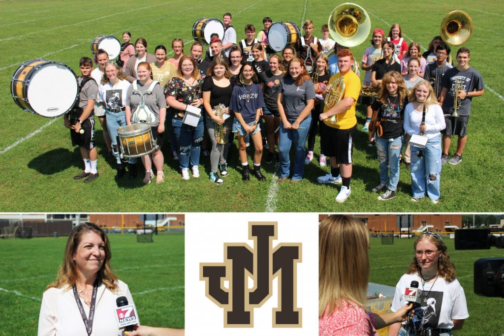 Picture of the band on the practice field. Tracey Filben and Paige Wallace are being interviewed by channel 7.