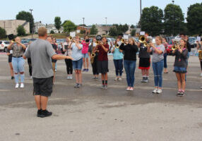 The Marching Monarchs rehearse, for their halftime show, in the school's student parking lot.