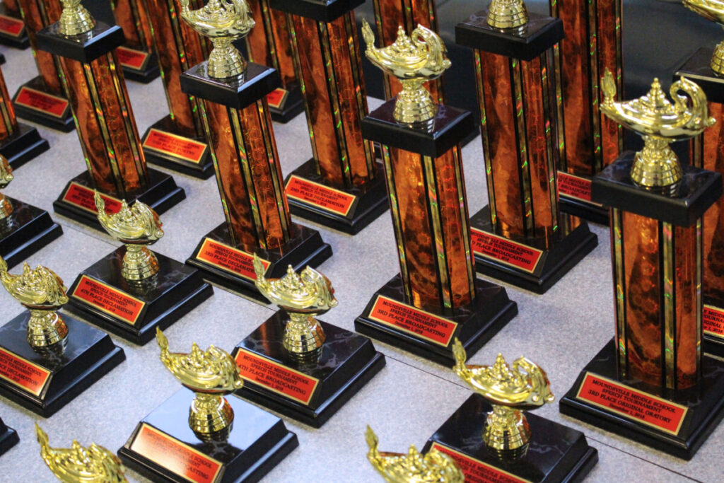 Moundsville Middle Speech Tournament trophies lined up on a table. The trophies are black and orange with a plastic golden medallion on top.
