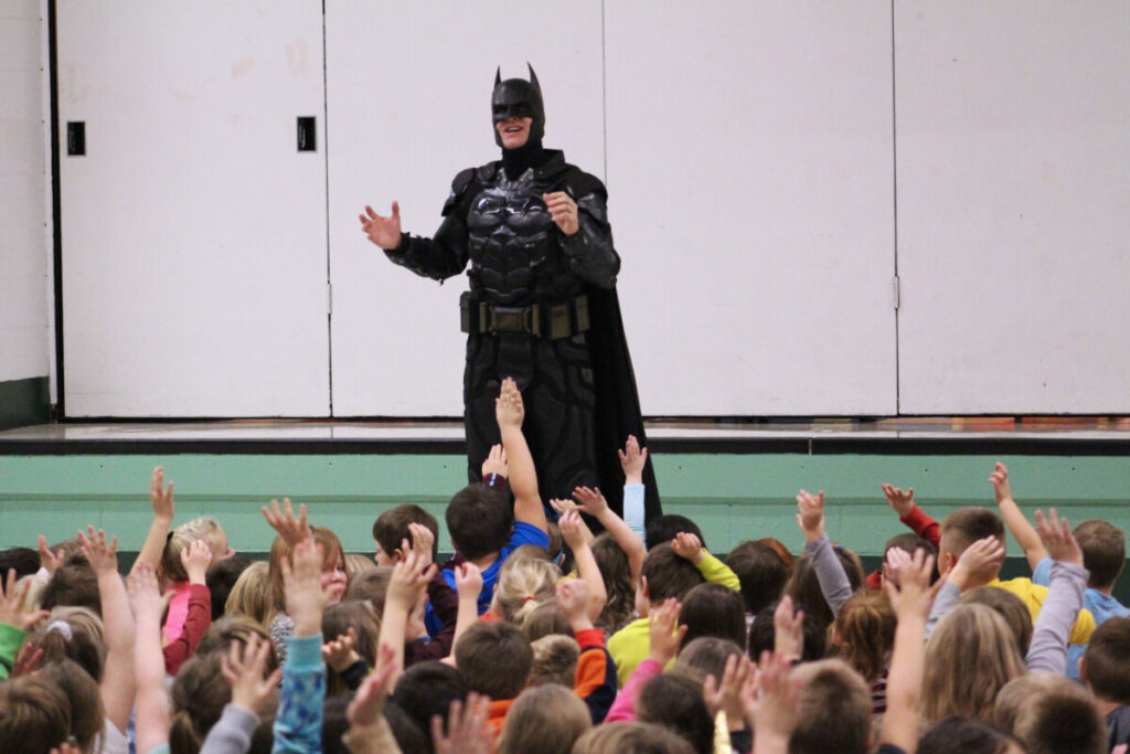 Batman talks to a large group of students about not being a bully.